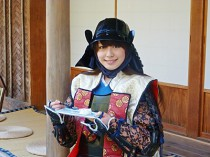 鎧姿でお茶菓子をほおばる遠藤恭葉さん